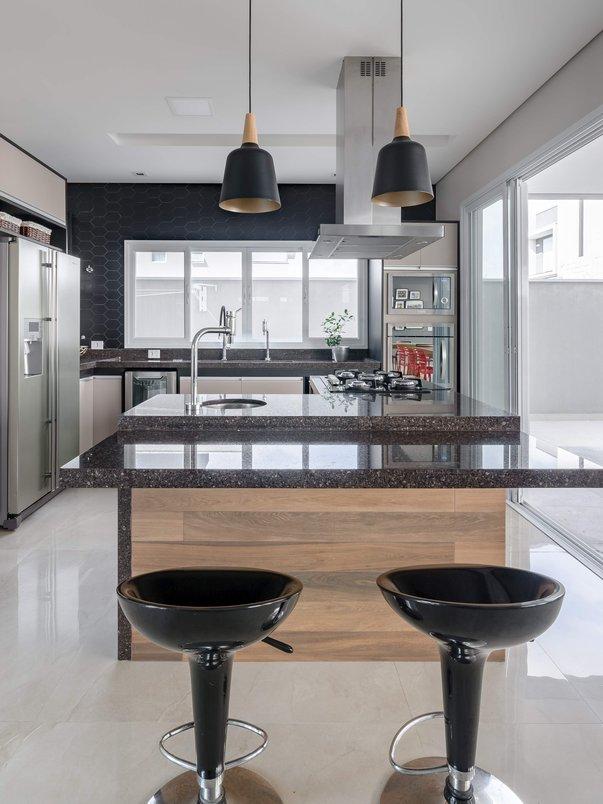 Cozinha ampla com acabamento em preto e tons terrosos. Foto: R. Rizzutti