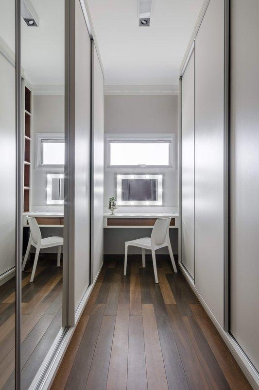 Closet com penteadeira e piso madeirado. Foto: R. Rizzutti