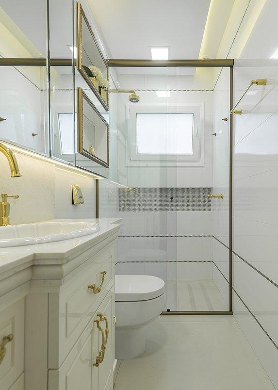 O banheiro segue o estilo clássico marcante da maior parte da residência. Porcelanato: City off White | Pastilhas: Gioielli Oro