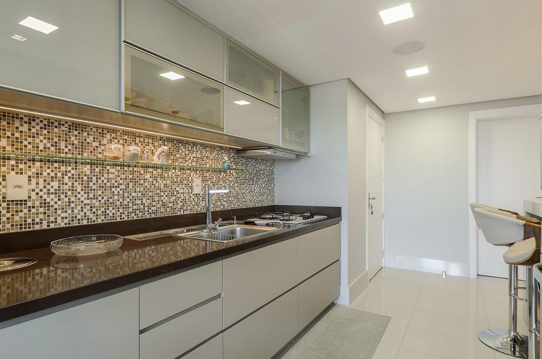 O elegante visual da pastilhas somadas à bancada marrom deram o requinte necessário à esta cozinha integrada.
