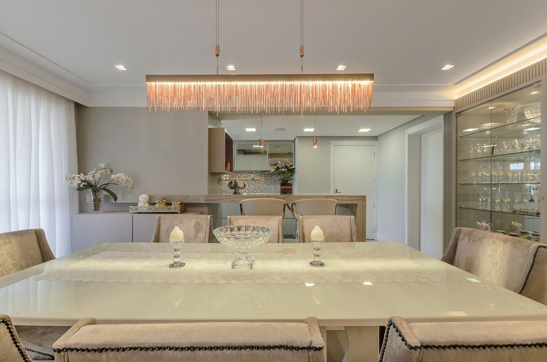 Visual do living mostrando a cristaleira e a cozinha. Luminária moderna. Sala de jantar clara branca.