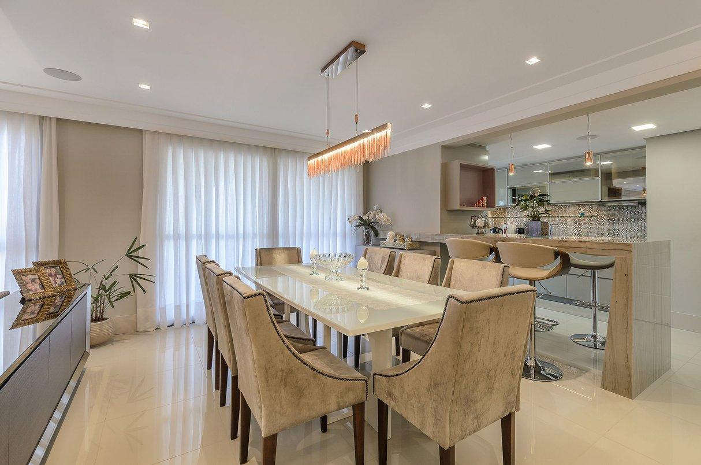 O espaço para jantar fica no meio do living integrando cozinha e home theater.