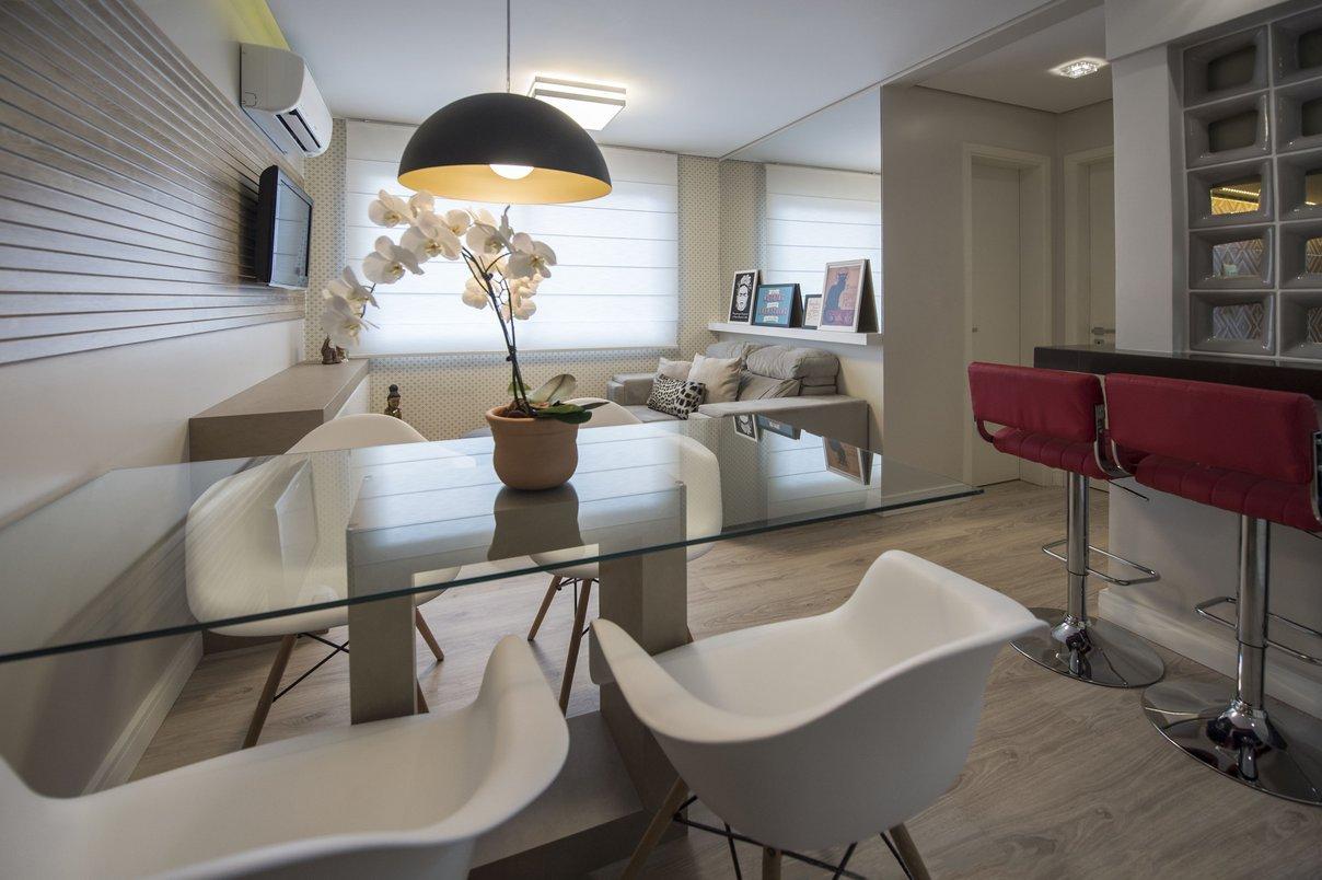 Ambiente integrado e leve fazendo uso de cores em tons pastéis, vidro e espelho. A parede que mais tem unidade na sala foi revestida com Clapboard Canela 30x90cm RET, e Cobogós Planalto Argento 21x21cm. Portobello