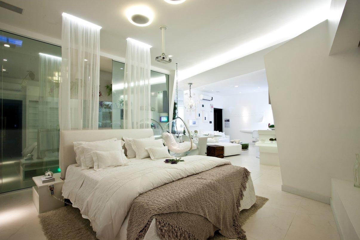 O tecido na cabeceira da cama simula um tradicional dossel dando uma releitura contemporânea para um item clássico. Os vidros espelhados dividem o banheiro do quarto, configurando uma barreira física, mas não visual entre os espaços. Porcelanato: Bianco Carrara.