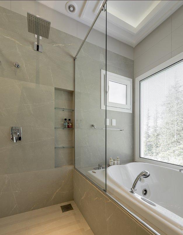 Banheiro master conta com ampla banheira para os moradores apreciarem a paisagem durante o banho. Porcelanato: Gris Armani