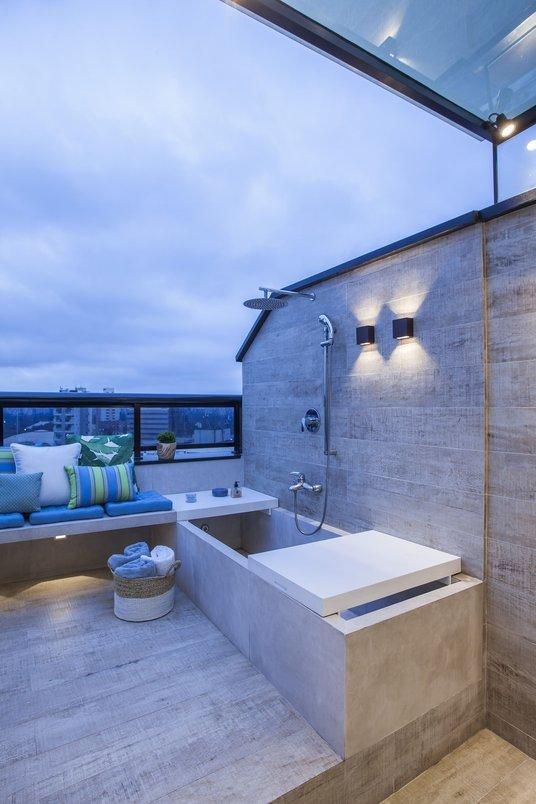 A banheira em alvenaria, revestida em porcelanato, conta com um chuveiro de água quente e fria, o que permite aproveitá-la mesmo em dias mais frios.