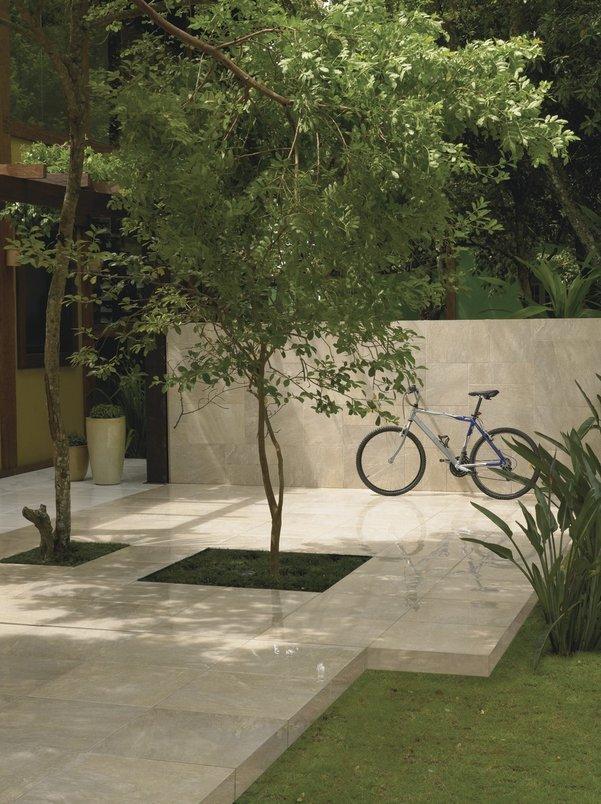Árvore no jardim da casa e bicicleta encostada na parede da área externa.