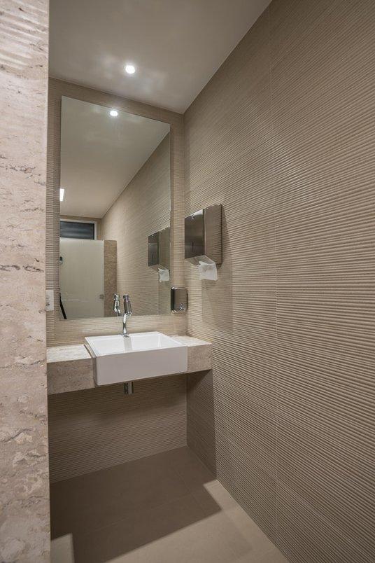 Vestiário de apoio à piscina. No piso, o porcelanato Portobello Camel, da linha Colorless. Nas paredes, o Bamboo Stone, da linha Wall Mosaic.