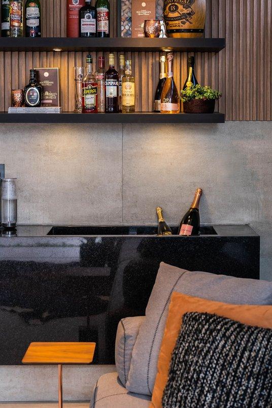 A área de bar, tão importante quanto todos os itens deste projeto, ganha destaque com seus elementos sólidos e com a diversidade de texturas que se complementam. A criação de duas Champanheiras fazem desta área, um espaço multifuncional, para gelar bebidas, expor seus melhores rótulos e ainda ter aquele cantinho do café.
