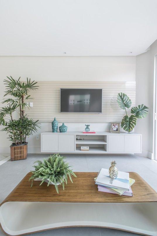 Plantas na sala branca com móveis de madeira.