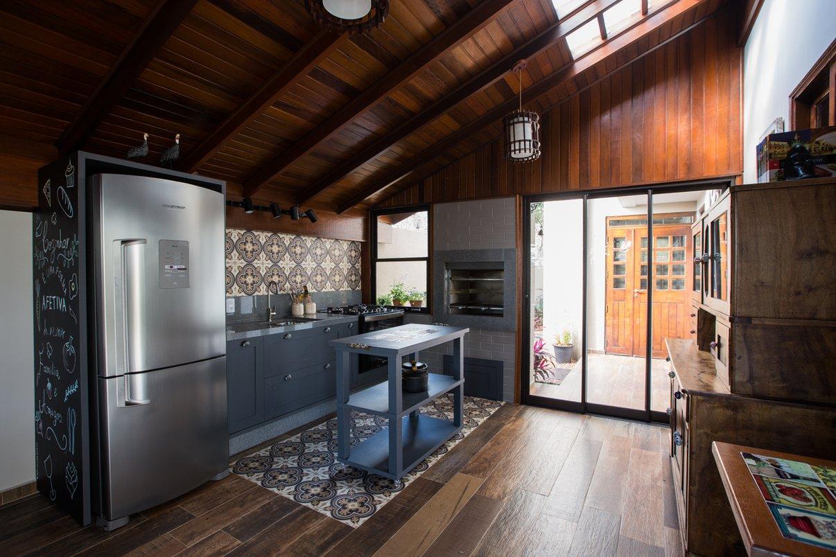 Edícula atendendo a necessidade de um espaço para receber família e amigos contando com uma cozinha completa com churrasqueira com acesso pelo jardim da residência.