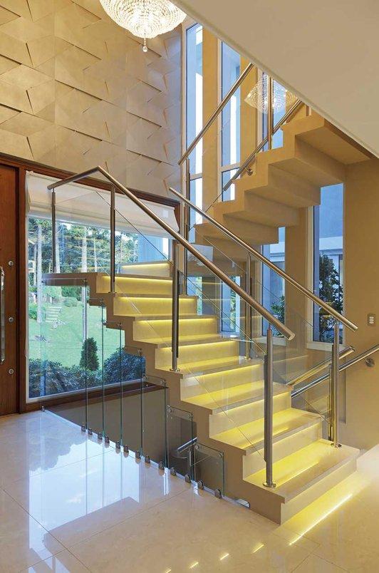Escada esculpida em porcelanato Perlino Bianco 90x90, com iluminação embutida