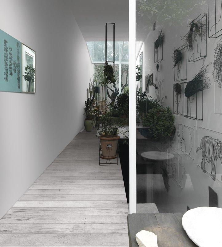 Corredor da escada com quadros e plantas. Piso com porcelanato - madeira branco e cinza.