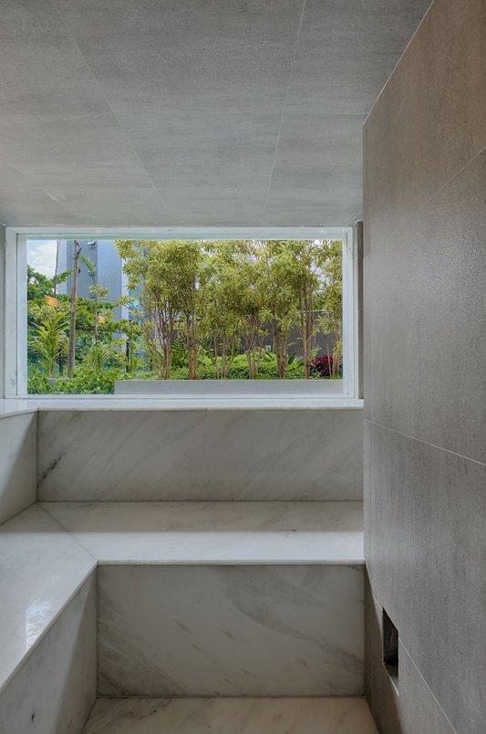 Sauna com paredes e teto revestidos em porcelanato Portobello St Remy Argento, 60x60cm. Piso e paredes em mármore branco.