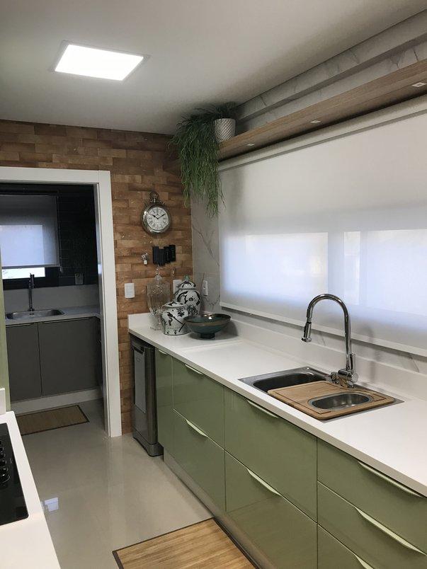 Cozinha com parede de tijolos aparentes, móveis em tom verde pistache e bancada em quartzo branco.