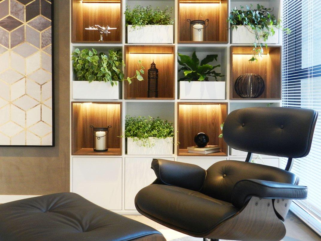 Detalhe da estante com cachepôs e da poltrona Eames Lounge Chair