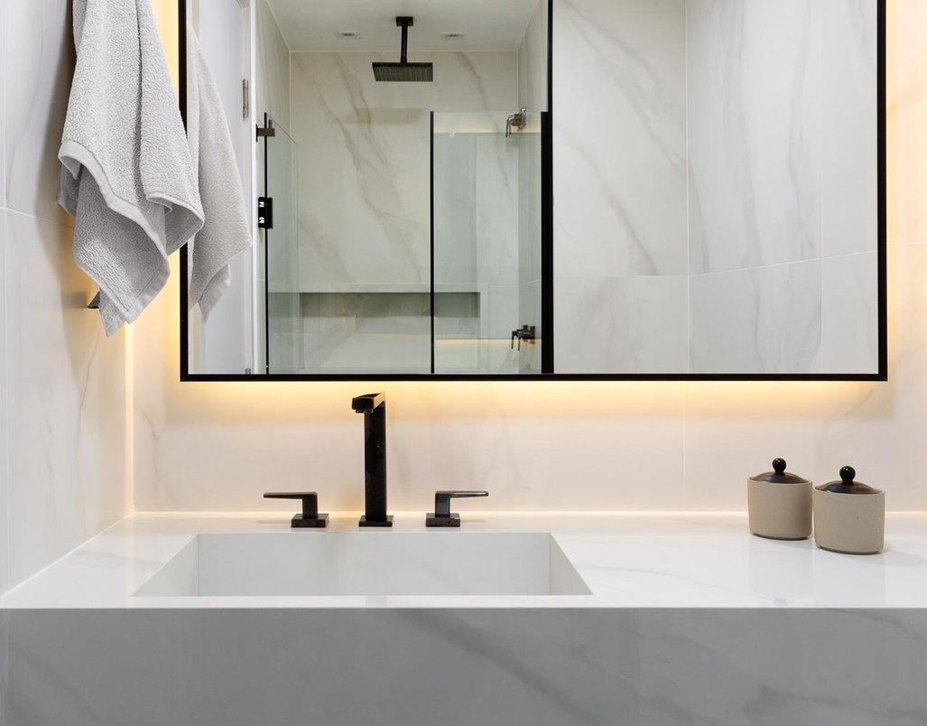 Bancada esculpida, piso, paredes e nicho usando um único revestimento. Iluminação indireta, nicho iluminado e metais pretos deram um charme nesse lindo banheiro.
