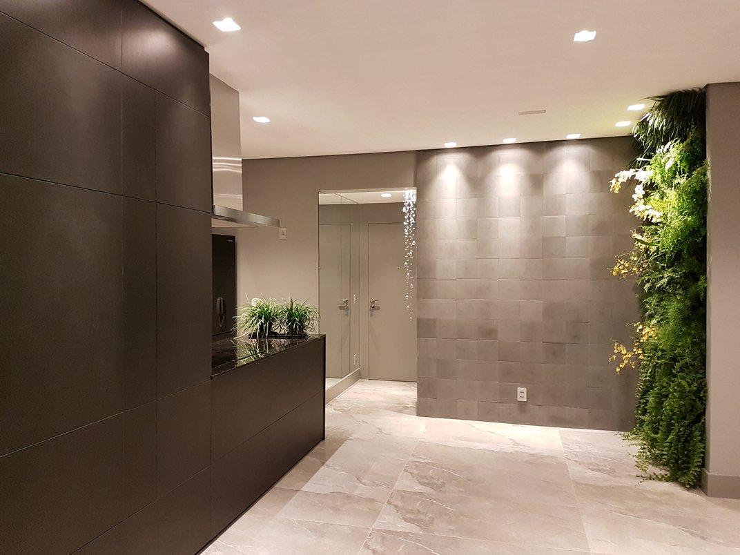 Sala de estar, com bancada de cooktop em granito e mdf pretos. O piso Noir St Laurent 60 x 1.20 foi usado em todo o apartamento. A cliente adora plantas então fizemos jardins verticais na sala e na varanda. E na bancada também foi previsto um local para plantas ou uma hortinha de temperos.