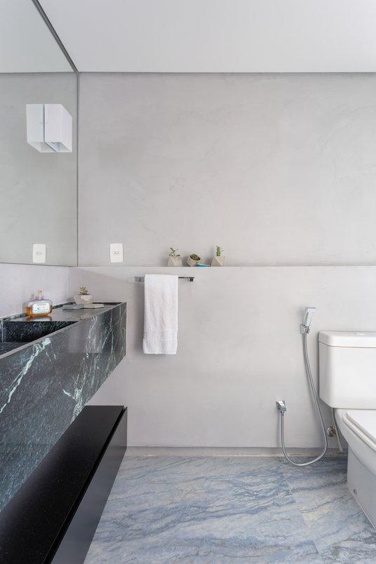 Banheiro com inspirações na história de nadador do cliente onde o Azul Boquira trouxe esse ar de cachoeira
