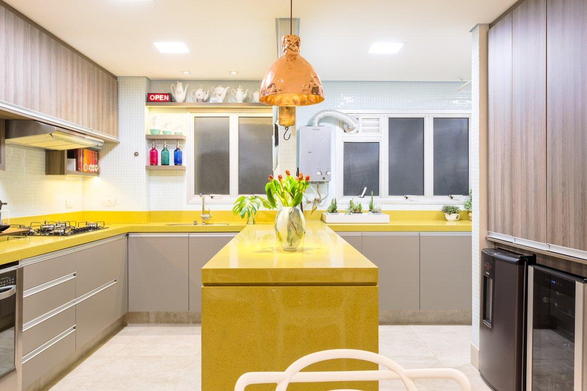 Uma cozinha toda aberta em tons de concreto onde o amarelo da bancada em padra sobressai