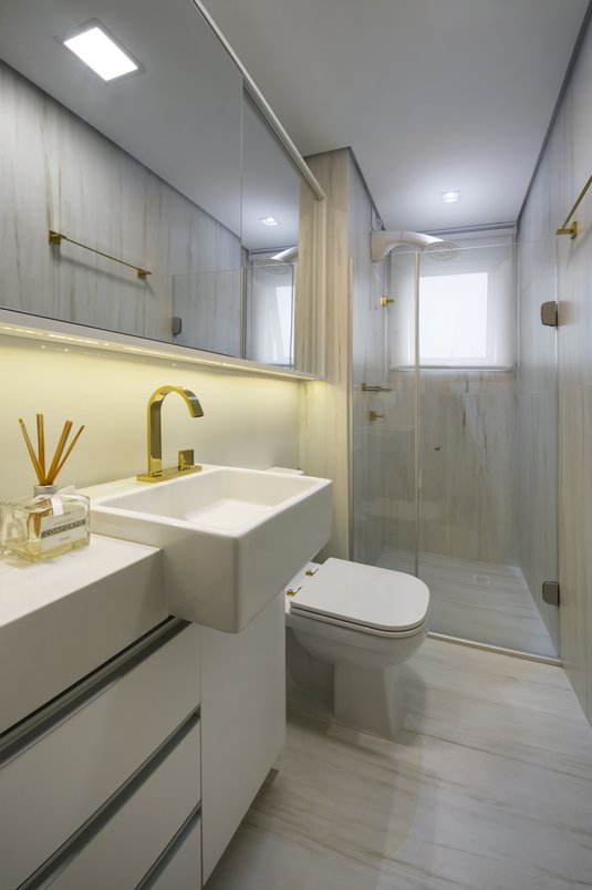 Piso e parede revestidos com Bianco di Ariston 60x120cm NAT RET. O móvel branco recebeu silestone branco e todo o ambiente metais dourados harmonizando com os revestimentos.