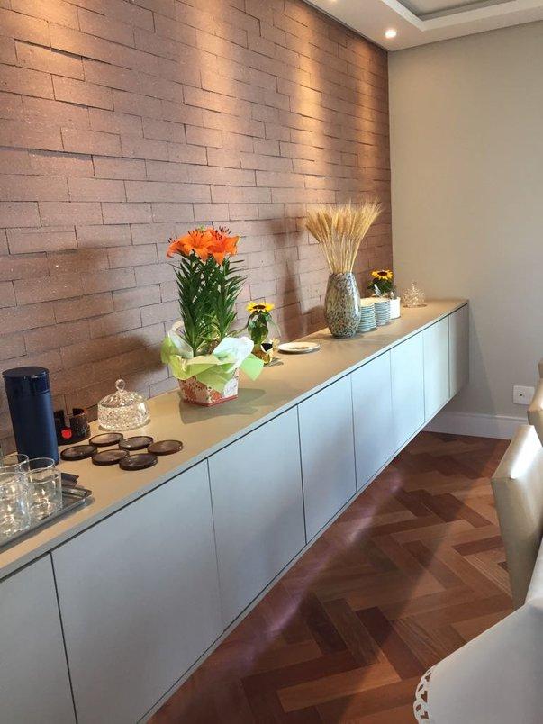 Ambiente moderno em contraste com revestimento rústico em uma das paredes.