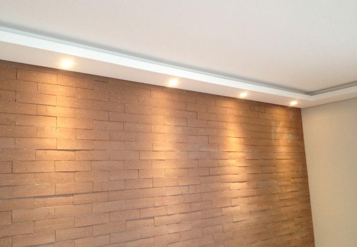 Pontos de led no forro posicionados próximo a parede valorizam a cor e o relevo do revestimento.